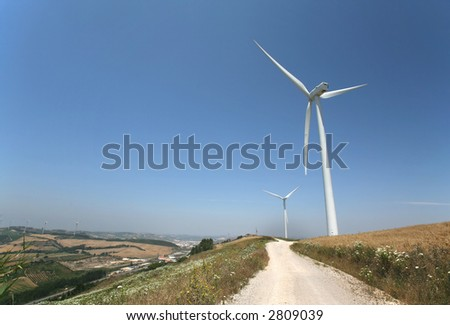 photo of a road with wind turbines