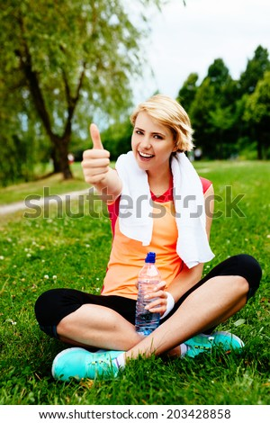 Photo of a satisfied woman runner sitting on the grass after a park run - stock photo