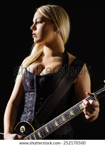 Photo of a sexy blond female playing a black electric guitar wearing a black corset.