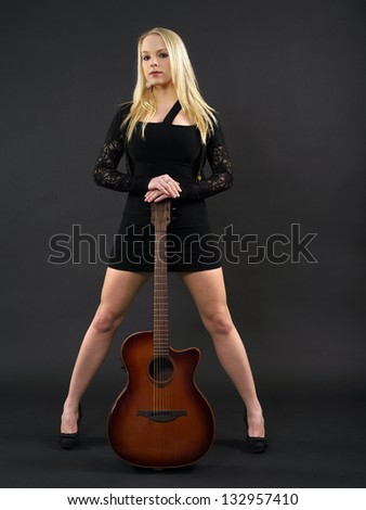 Photo of a sexy blond female standing and holding an acoustic guitar over a black background.