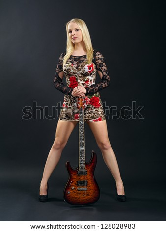 Photo of a sexy blond female standing and holding an electric guitar over a black background.