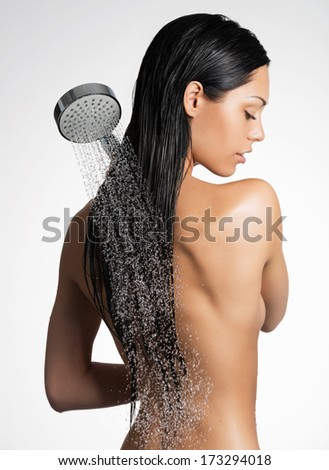 Photo of a sexy woman in shower washing long hair  - stock photo