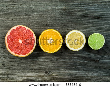 Photo of a sliced grapefruit, orange, lemon, and lime in a row on a old rustic slab of barn board. - stock photo