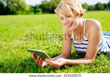 Photo of a smiling woman lying on the grass and using a digital tablet