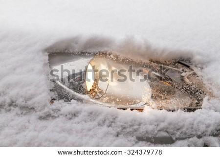 Photo of a snowy car's snowy headlight  - stock photo