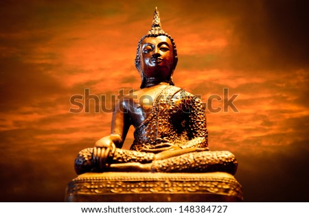 Photo of a statue of the Buddha meditating with sunset in the background