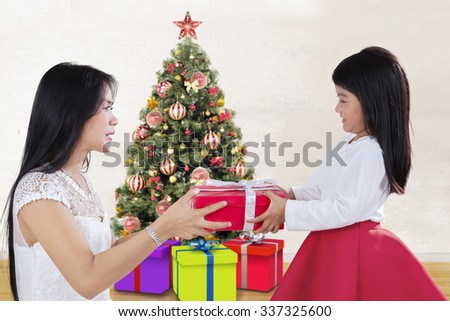 Photo of a sweet girl offering a christmas gift on her mother at home with a christmas tree background - stock photo
