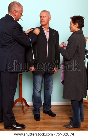 Photo of a tailor drawing with chalk on the mans jacket during a bespoke suit fitting. - stock photo