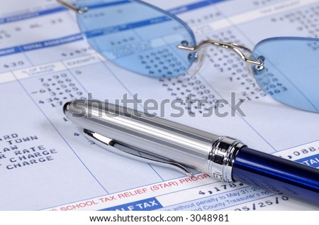 Photo of a Tax Related Form with Eyeglasses and a Pen - Finance Related