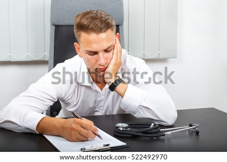 Photo of a tired young male doctor in his medical office