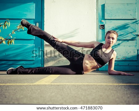 Photo of a toned young woman outside on the pavement doing leg exercises late in the day.