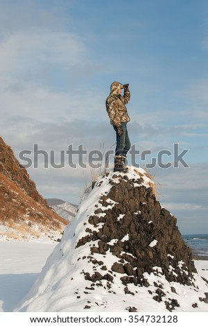 Photo of a tourist standing on the cliff, watching the horizon