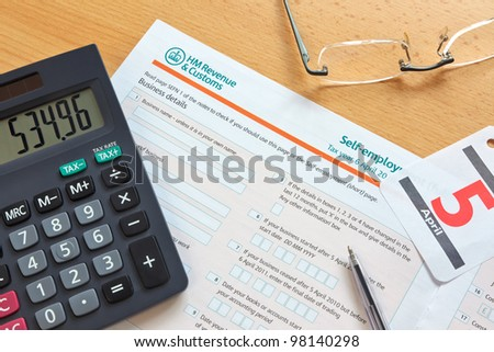 Photo of a UK self employment tax form, the deadline for the tax year is 5th April as shown by the calendar. - stock photo
