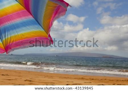 photo of a umbrella on a sandy beach - stock photo
