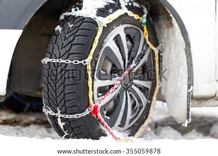 Photo of a vehicle tire with snow chains on a frozen road - stock photo
