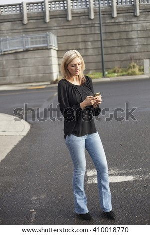 Photo of a very attractive blonde woman in a black shirt and jeans sending text messages on her cell phone. - stock photo