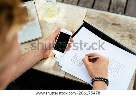 Photo of a web designer drawing a blueprint of a new mobile application - stock photo