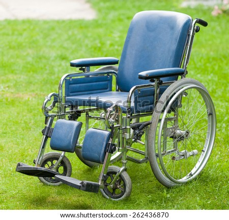 Photo of a wheelchair on green grass - stock photo