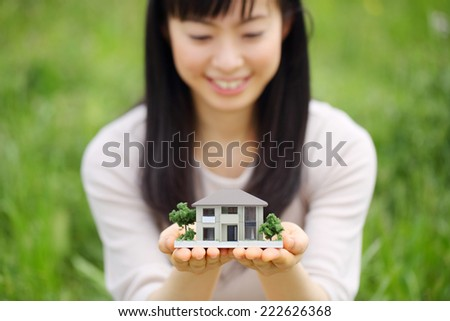 Photo of a white miniature house held by a woman