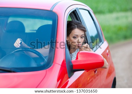 Photo of a woman applying lipstick sitting in car - stock photo