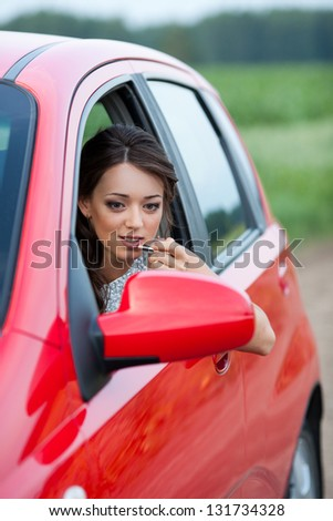 Photo of a woman applying lipstick using the car's mirror - stock photo
