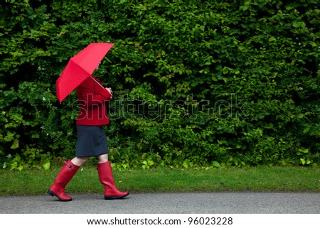 Photo of a woman in red walking along a road with her umbrella up as it starts to rain on an overcast day. Slight motion blur on her legs. - stock photo