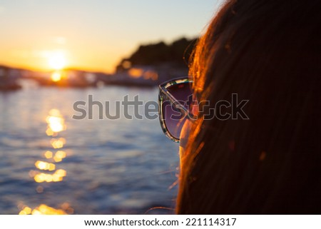 Photo of a woman looking at sunset on a beach
