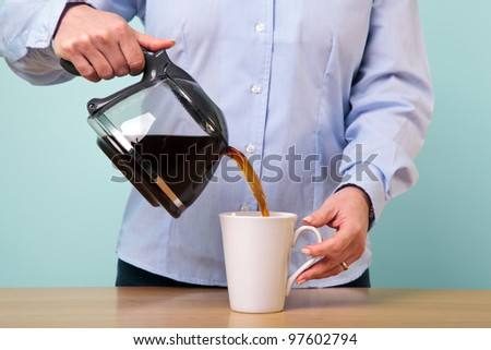 Photo of a woman on her break pouring herself a mug of hot filtered coffee from a glass pot. - stock photo