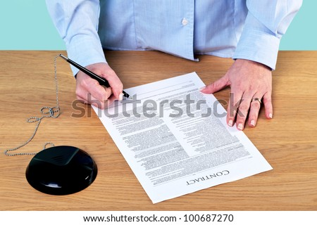 Photo of a woman signing a contract, the text on the contract is illegible. - stock photo
