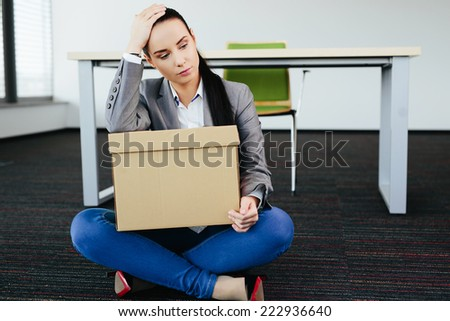Photo of a worried woman who has been fired  sitting on the floor - stock photo
