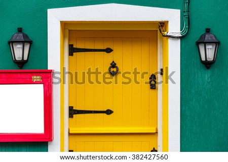 Photo of a yellow front door and two decor lamps  - stock photo