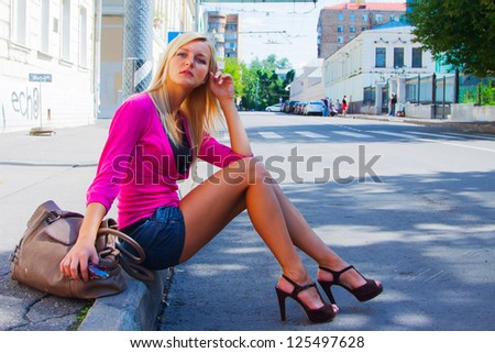 Photo of a young and beautiful girl walking down the street - stock photo