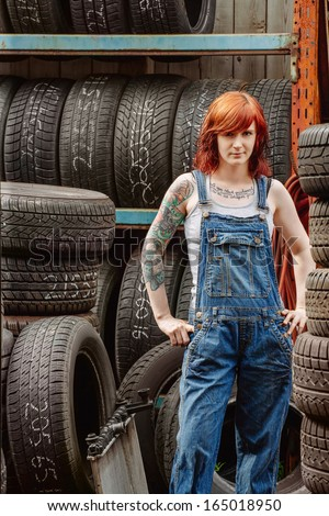 Photo of a young beautiful redhead mechanic wearing overalls and standing in an old garage. Attached property release is for arm tattoos.  - stock photo