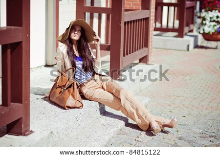 Photo of a young beautiful woman brunette fashion fabrics in today's casual elegant hat with a bag - stock photo