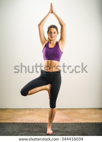 Photo of a young beautiful woman exercising and doing the Yoga tree position. - stock photo