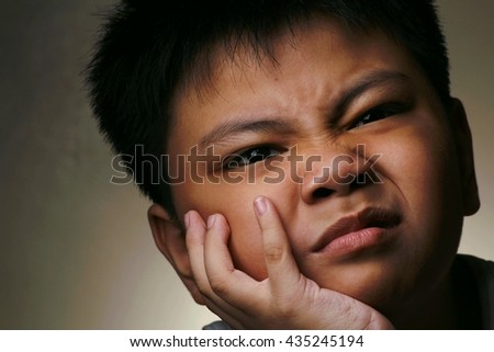 Photo of a young boy resting his face with a silly expression on his hand