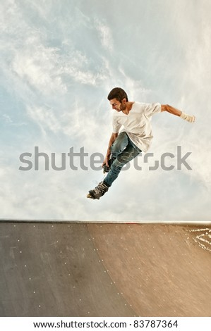Photo of a young boy with rollerblades jumping high on the skate ramp. Frozen in the hang time. Vintage look to it, with copy space to the bottom part of the image. - stock photo