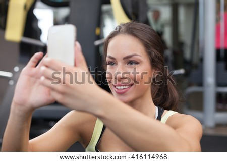Photo of a young determined woman who is using her mobile phone to capture the result of her intense workout in the gym