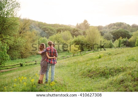 Photo of a young family enjoying a stroll in the park on a sunny summer day. Big family tree on the background - stock photo