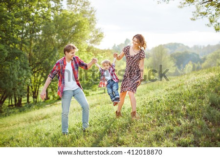 Photo of a young family enjoying holidays in the park on a sunny summer day countryside - stock photo