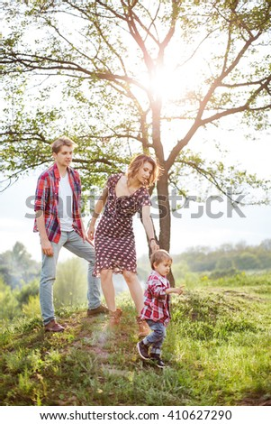 Photo of a young family enjoying holidays in the park on a sunny summer day near big family tree - stock photo