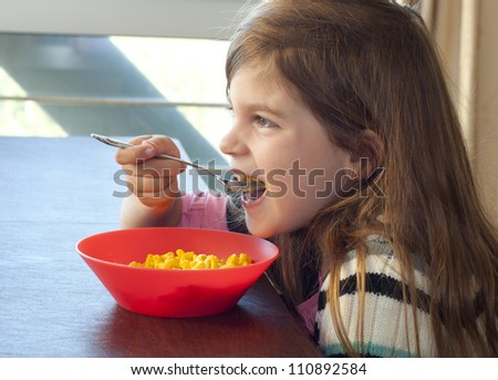 Photo of a young girl eating macaroni and cheese for lunch or dinner