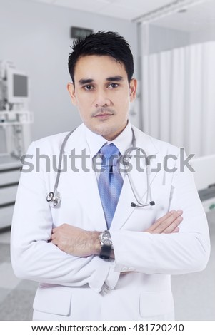 Photo of a young male doctor looking at the camera while wearing uniform and standing in the clinic room