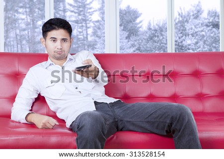 Photo of a young man sitting on sofa while watching tv and looks bored, changing the tv channel by using a smartphone - stock photo