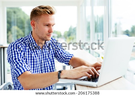 Photo of a young man typing on a laptop - stock photo