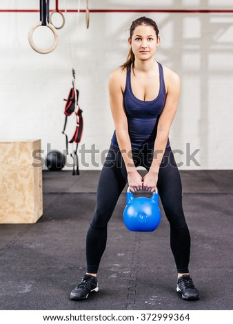Photo of a young woman exercising with a kettle bell at a gym.   - stock photo