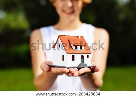 Photo of a young woman holding a miniature house - stock photo