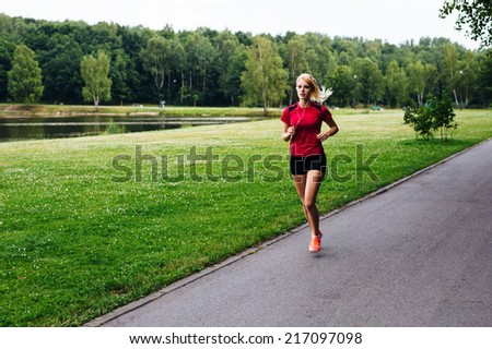 Photo of a young woman jogging in the park - stock photo
