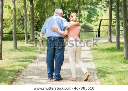 Photo Of A Young Woman With Her Disabled Father Standing In Park
