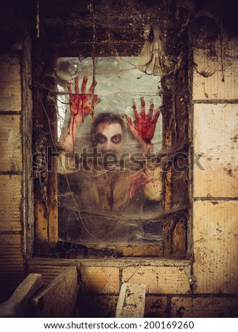 Photo of a zombie outside a window that is covered with blood, spiderwebs and filth. - stock photo